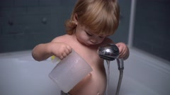little baby showers and drinking water from a jug in the bath - stock footage