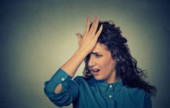 silly young woman, slapping hand on head having duh moment made mistake - stock photo