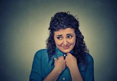 Lack of confidence. Shy young woman feels awkward - stock photo