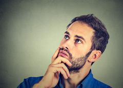 man resting chin on hand thinking daydreaming, staring thoughtfully upwards - stock photo