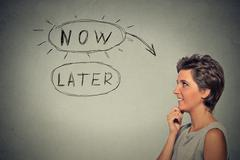 Now or later. Happy woman thinking looking up - stock photo