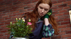Beautiful redhead girl looking after flowers Stock Footage