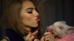 Sexy girl and a pig in a pink fur coat Stock Footage