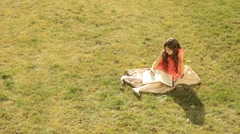 Little girl sitting on the grass, and wrote in his diary his dreams Stock Footage