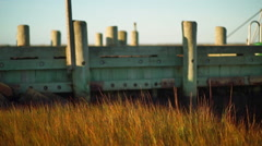 Static Shot Of Breeze Blowing Tall Grass In Salt Marsh By Dock Stock Footage