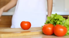 Woman hands slicing tomato in kitchen - stock footage