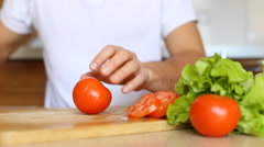 Amateur cooker slicing red tomato on bamboo cutting board - stock footage