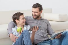 Cute parent and child are entertaining with gadgets - stock photo