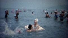 1961: Mom teaching son to swim in ocean kicking legs hard. - stock footage