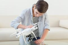 Pretty male teenager is using a drone - stock photo