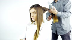 Woman in salon getting hair straightened by professional hairstylist 4K Stock Footage