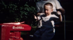 1959: Toddler riding toy red Farmall tractor grandpa watching. Stock Footage