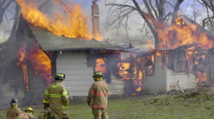 Firefighters watch as house roof burns Stock Footage