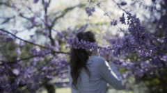 Camera passes by a girl next to a blossoming tree in springtime - stock footage