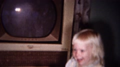 1959: Blonde toddler girl dancing to TV music in living room. Stock Footage