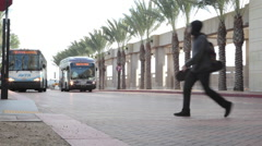 Skateboarder walks by the buses arriving at LA Union Station terminal Stock Footage