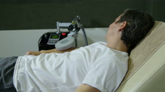 Man with injured hand on pulse electromagnetic therapy, patient lying in bed. Arkistovideo