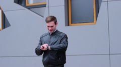 Very Nice Man Using Smart Watches. he Presses a Finger on the Screen, Standing Stock Footage