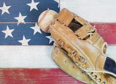 Old worn baseball mitt and baseball on faded wooden boards painted red, white - stock photo