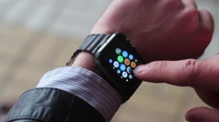 A Man Adjusts a Smart Watch. on the Colored Icons Are Visible. New Stock Footage