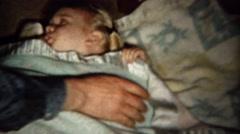 1961: Mom tucking in baby girl blanket sucking thumb bedtime. Stock Footage