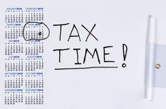 White board with calendar marked for tax reminder in April - stock photo