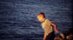 1961: Devious troublemaking boys throwing rocks in lake at sunset. Stock Footage
