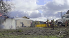 Two firemen teams water a burning home Stock Footage