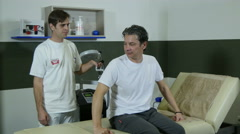 Physiotherapist puts device on back of patient, pulse electromagnetic therapy. Stock Footage