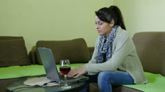 Pretty girl  works for laptop, she wears jeans and sweater, glass of red wine on Stock Footage