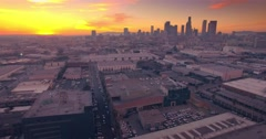 Aerial industrial warehouses rooftops Los Angeles downtown skyline sunset 4K UHD Stock Footage