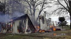 Medium shot of smoldering house - stock footage