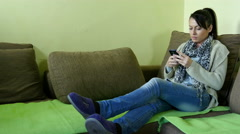Pretty girl in casual clothing coming and lying on the bed, using cell phone. Stock Footage