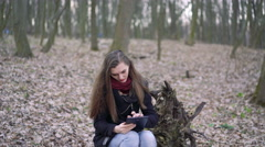 Beautiful girl sitting on a stump and using tablet. 4k - stock footage