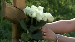 Woman fixes white roses on wooden tombstone - stock footage