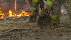 Firemen roll up hoses Stock Footage