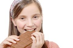 Preteen  girl eats chocolate, isolated on white Stock Photos