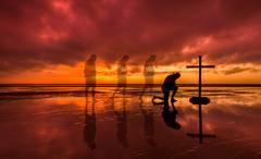 Kneeling Salvation Cross - stock photo