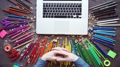 Workplace with colored pencils, laptop, palette on wooden table Stock Footage