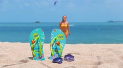 Woman on a tropical beach. FlipFlop background. Beautiful girl goes from the sea - stock footage