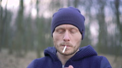 A young man smokes a cigarette in the forest. 4k Stock Footage