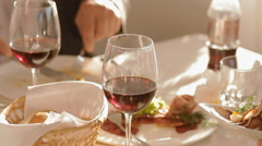 Plate with food and glass of red wine on the table - stock footage