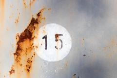 Number 15 on old painted and rusted metal panel - stock photo