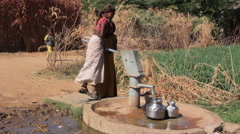 Indian rural girls pour water from the pump to the jugs.Rajasthan.Maunt-Abu.2016 Stock Footage