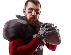 American football player posing with ball on white background Kuvituskuvat