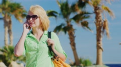 Woman tourist in sunglasses talking on the phone on the background of sky and Stock Footage
