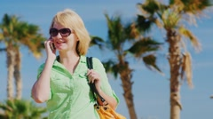 Happy tourist speaks by phone on a background of blue sky and palm trees - stock footage