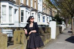 Girl in black dress with polka dots and sunglasses - stock photo