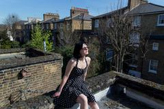 Girl in black polka dot dress  sitting on the roo - stock photo