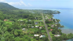AERIAL: Oceanfront marine fishing village on tropical island Tahiti Stock Footage